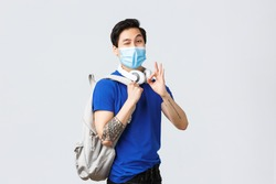 Back to school, studying on covid-19, education and university life concept. Happy handsome asian male student show okay sign, likes new year college, wink in medical mask, go classes with backpack