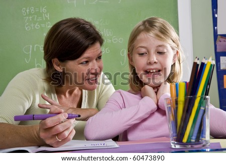 Back to school - teacher teaching 8 year old student in classroom