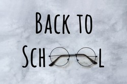 Back to school text and stylish black round eyeglasses spectacles on marble background. Creative concept education. Top view Greeting card.