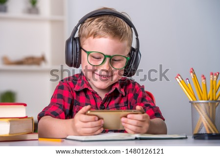 Back to school. Thinking child doing homework online with smartphone. Pupil in headphones. Learn English. Innovation teacher concept. Addicted kid gaming. Boy listening to music, playing