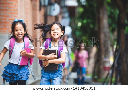 Back to school. Two cute asian child girls with school bag holding book and walk together in the school