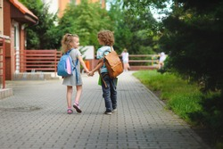 Back to school. Two young students go to school hand in hand. They about something briskly talk. Behind the back of everyone satchel. Little first graders. Schoolchildren.