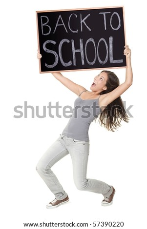 Back to school / university / college. Excited university student holding chalkboard saying back to school. Young female model. Isolated on white background.