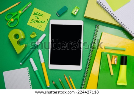 Back to school with digital tablet and green stationery on desktop.
