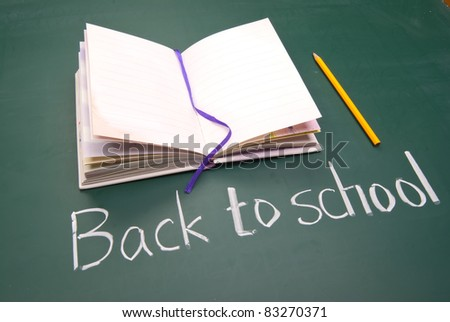 Back to school words, Book and pencil on blackboard.