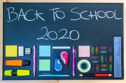 Back to School 2020 written on a chalkboard with pens and others school objects