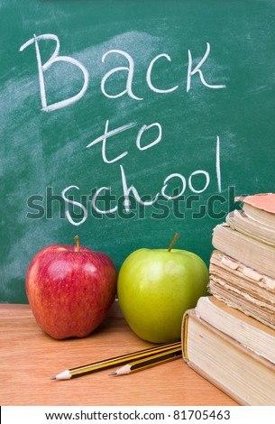Back to school written on board with books, apples and pencils