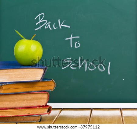 Back to school written on chalkboard with green apple and  books