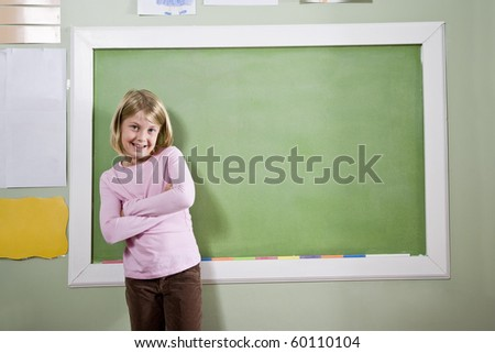 Back to school - 8 year old girl smiling in classroom, standing by blackboard