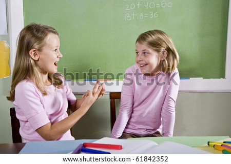 Back to school - 8 year old girls in classroom talking and smiling