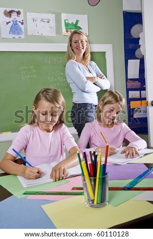 Back to school - 8 year old girls writing in notebooks in classroom with teacher watching