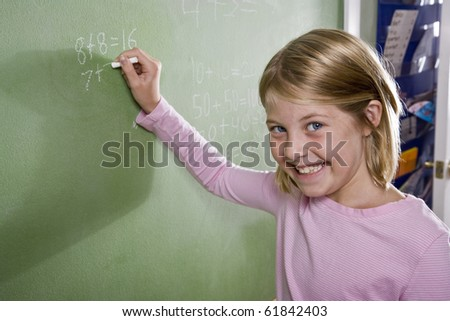 stock photo : Back to school - 8 year old girls writing on blackboard in classroom, doing math