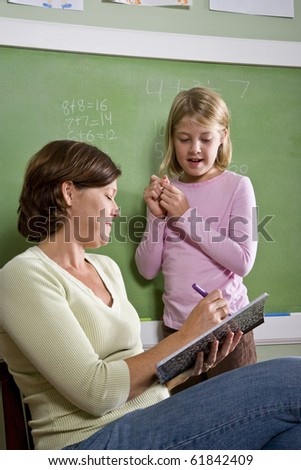 Back to school - 8 year old student and teacher by blackboard in classroom