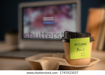 Back to Work Concept. Closeup of Welcome Note on Takeaway Coffee Cup in Office Desk. Message from a Colleague or Boss   Stock photo ©