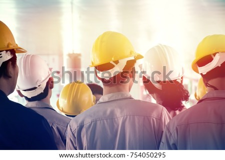 Back turned group of young workers or engineers with yellow and white helmets  standing in construction site, lighting effect