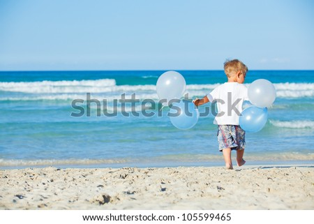 Back vie of cute little boy plays with ballons on the beach