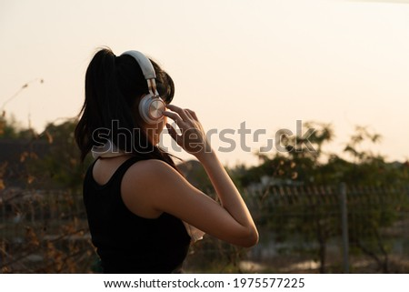 Back view and focus of young pretty Asian woman in sportswear, wearing headphones standing listening to a music while admiring nature view in front of her after take a rest from running in the evening Stock photo ©