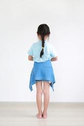 Back view asian little child girl wearing jacket shirt tied around waist standing indoor.