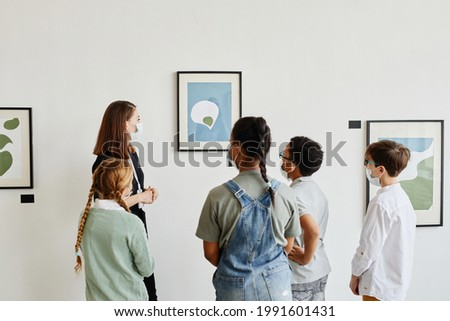Back view at diverse group of children wearing masks in art galley and looking at paintings with female teacher Stockfoto ©
