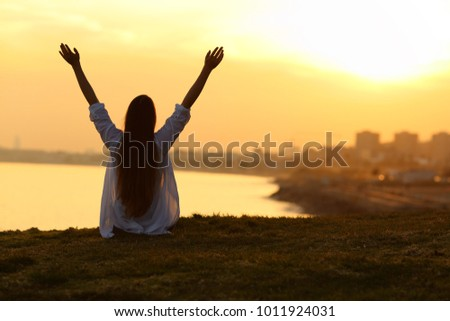 Back view backlight portrait of a happy single woman seeing the city at sunset and raising arms with a warm light in the background