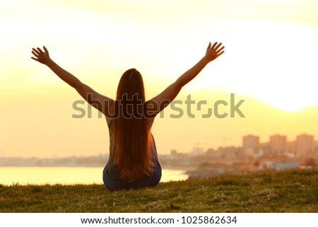 Back view backlight portrait of a single cheerful woman raising arms watching the city at sunset with a warm light in the background
