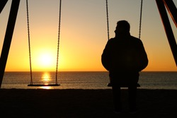 Back view backlighting silhouette of a man alone on a swing looking at empty seat at sunset on the beach in winter