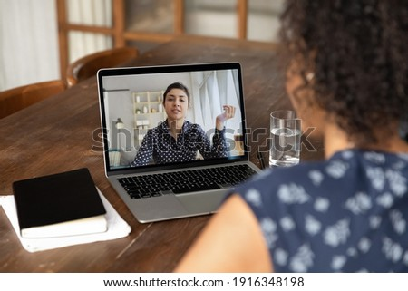 Back view close up African American woman making video call to Indian colleague, using laptop and webcam, diverse workers or friends chatting online, involved in conference, consulting client