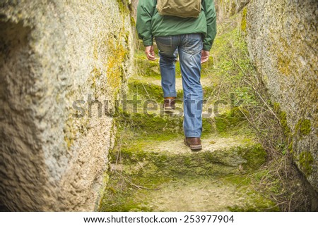 Back view Close up low angle man walking up green grass and moss ancient stones steps Senior wear windcheater with rucksack blue jeans brown leather shoes between wall going up stairway