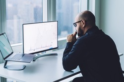 Back view concentrated bearded male trader analyzing data on computer monitor while sitting at desk near window in modern workplace
