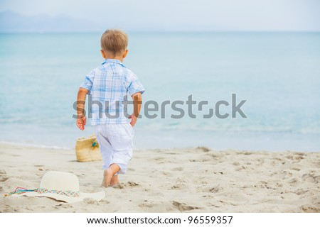 Back view cute 2 years old boy runing on tropical beach - stock photo