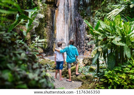 Back view family of father and his teenager son enjoying view of Diamond waterfall on Saint Lucia island in Caribbean