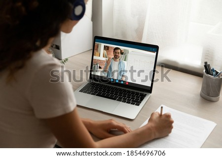 Back view focused young woman in headphones looking at computer screen, holding video call online private lesson with male teacher native speaker, learning foreign language distantly at home.