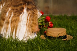 Back view from the back of a child girl with long blond golden wavy hair in a hat, against a background of green grass lawn, holding a bouquet of red tulips.