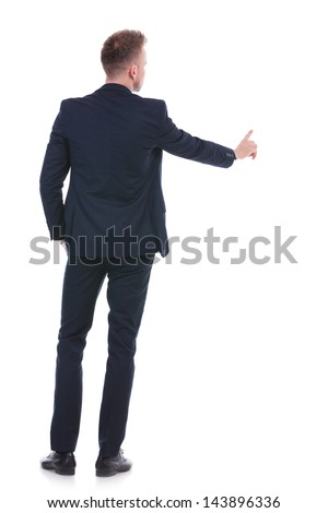 back view full length picture of a young business man pushing an imaginary button while holding a hand in his pocket. on white background