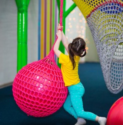 back view. funny girl with ponytails hangs on a rope and crawls on a big red ball.