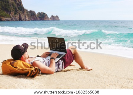 Back view, hipster young man lying on sandy beach leaning on backpack, with laptop computer, typing, blogging, browsing. Freelance, distance work concept. Sea view, ocean waves. Background, copy space #1082365088