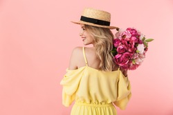 Back view image of a beautiful amazing young blonde woman posing isolated over pink wall background holding flowers.
