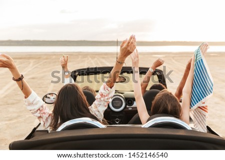 Back view image of a gorgeous pretty young pretty group of women friends driving the car with raised hands.