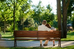 Back view mature couple on the park bench. Green summer park background.