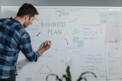 Back view modern businessman writing businessplan on white board.