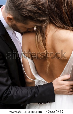 Back view of a beautiful bride being kissed by her groom on the shoulder.