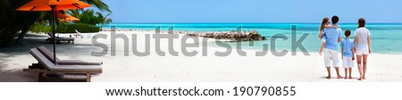 Back view of a beautiful family on a beach during summer vacation Wide panorama perfect for banners