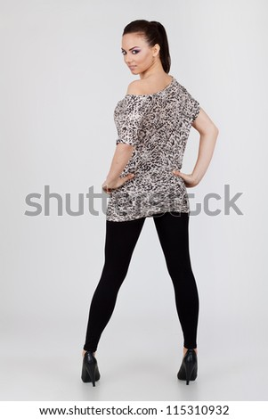 back view of a beautiful sexy young woman holding her hands on her hips and looking at the camera. on gray background