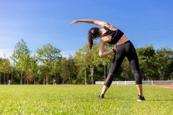 Back view of a beautiful young Asian woman stretching during her morning exercise at a running track's grass field on a clear sunny blue sky day, healthy lifestyle, copy space