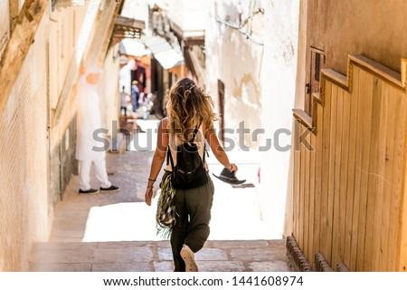 back view of a blonde tourist woman walking through the city on her vacation trip in the streets of morocco #1441608974
