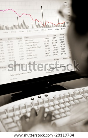 Back view of a broker watching the stock price falling in LCD screen.