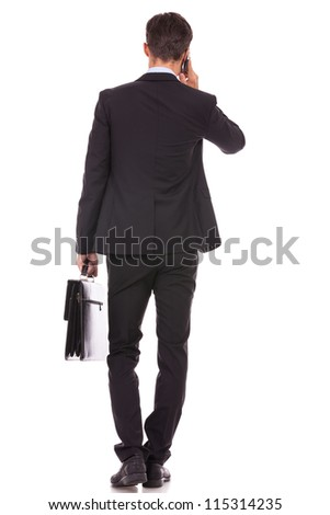 back view of a business man holding a briefcase and talking on his smartphone on white background