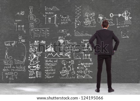 back view of a business man  looking at some charts , graphs and calculations on a blackboard