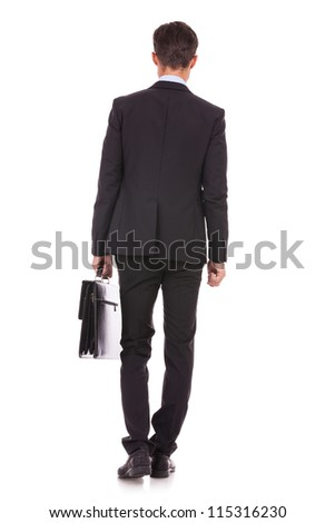 back view of a business man standing and holding a briefcase , looking away