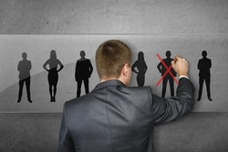 Back view of a businessman in front of a row of sihlouettes drawing red cross on one of the people. Dismissing, flunking, relieving. Big boss. Business staff.